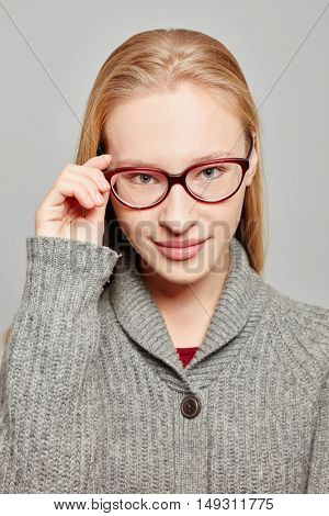 Young atractive woman with a hand on her glasses