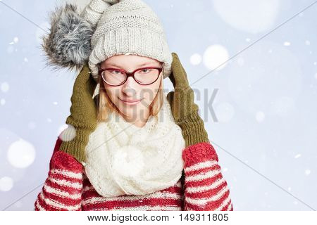 Young woman with a scarf and a cap in the snow in winter