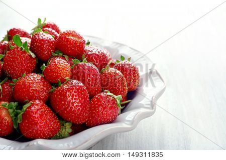 Plate with juicy strawberries on white wooden background