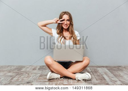 Happy attractive young woman holding laptop and showing peace sign