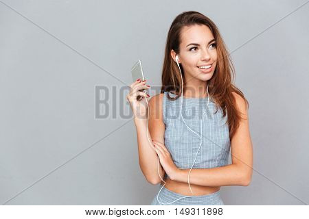 Smiling cute young woman listening to music from cell phone over grey background