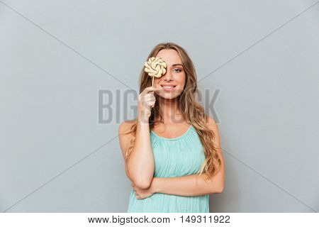 Funny cheerful young woman covered her eye with lollipop