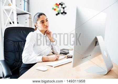 Beautiful concentrated businesswoman making notes and looking at computer screen while sitting at the office