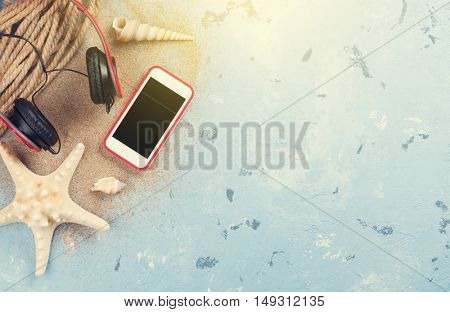 Travel vacation items on stone background. Smartphone, headphones and starfish. Top view with copy space. Sunny toned