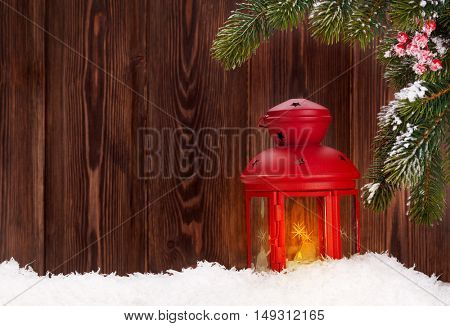 Christmas candle lantern, fir tree branch in snow. View with copy space