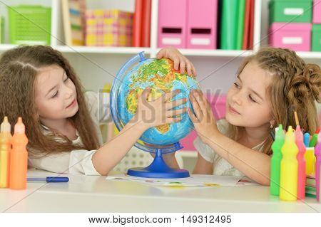 portrait of Cute girls  on lesson with globe