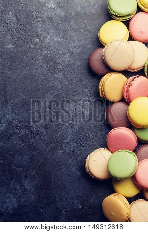 Colorful macaroons on stone table. Sweet macarons. Top view with copy space for your text. Retro toned