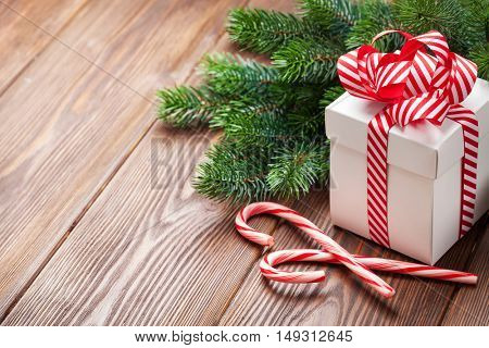 Christmas gift box, candy cane and fir tree branch. View with copy space