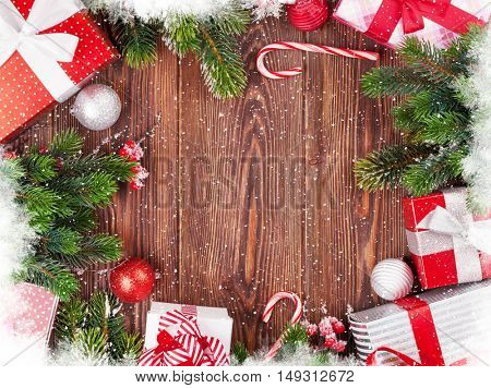 Christmas gift boxes, decor and fir tree branch on wooden table. Top view with copy space