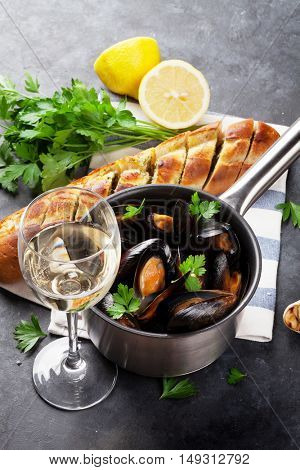 Mussels in copper pot and white wine on stone table