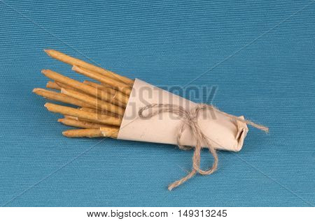 Salted Sticks In A Paper Bag On The Blue Textile Background.