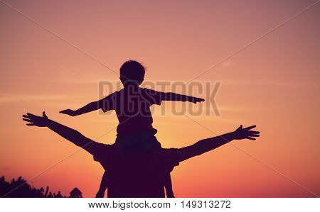 silhouette of father and son having fun at sunset sky