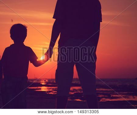 silhouette of father and son holding hands at sunset beach