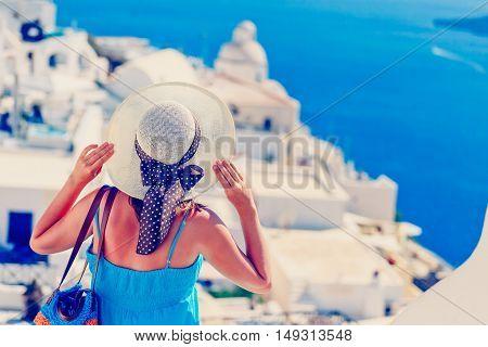 young woman enjoying view of Santorini, Greece, travel concept
