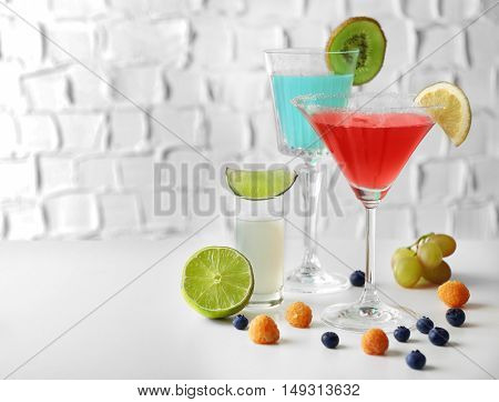 Delicious cocktails with berries on white table