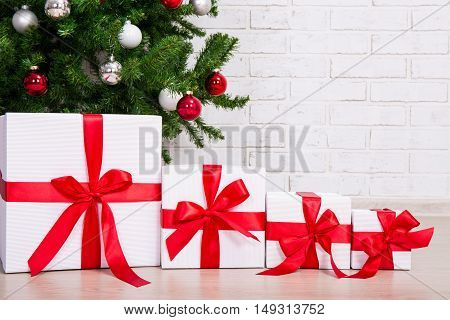 Close Up Of Gift Boxes Under Decorated Christmas Tree