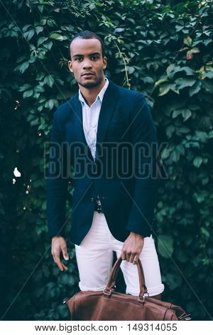 Confident and stylish. Handsome young African man in smart casual wear carrying bag and looking at camera while standing against green plant background outdoors