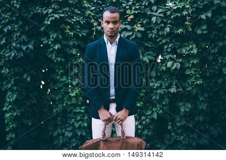 Always in style. Handsome young African man in smart casual wear carrying bag and looking at camera while standing against green plant background outdoors