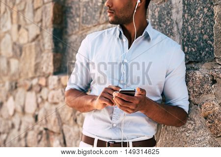 Man enjoying music. Close-up of handsome young African man in headphones carrying smart phone while standing against the stoned wall outdoors