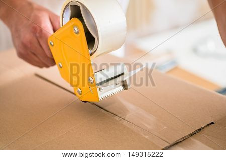 Man taping packing case