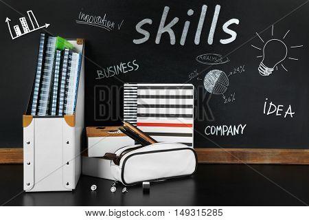 Skills. School supplies near blackboard, close up