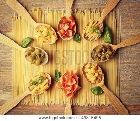 Different dry pasta on wooden spoons
