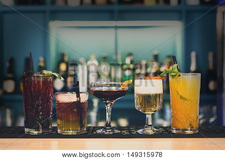 Closeup row of creative sweet exotic non-alcoholic and alcoholic party cocktails in restaurant at bar background. Glasses with beverages on bar table, refreshing drinks with straws.