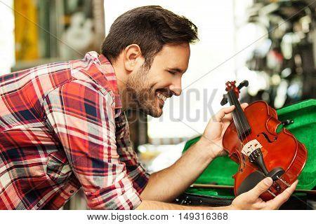 Young man is looking for violin in musical instruments store.