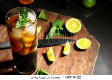 Kitchen board with cuba libre cocktail, knife, mint and lime
