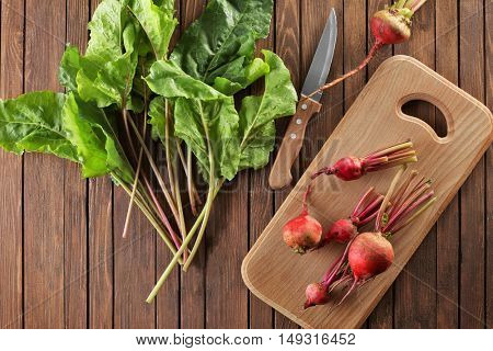Fresh beets and knife on wooden board