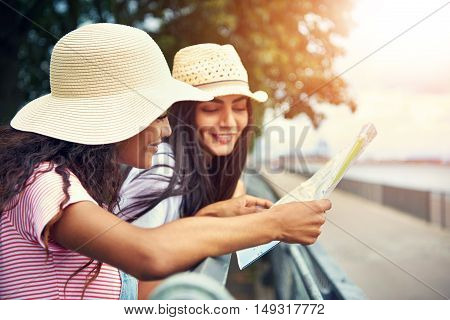 Women wearing floppy summer hats reading a map while standing against a railing by a running trail