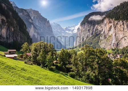 Great view of alpine village glowing by sunlight. Picturesque and gorgeous scene. Popular tourist attraction. Location place Swiss alps, Lauterbrunnen valley, Staubbach waterfall, Europe. Beauty world
