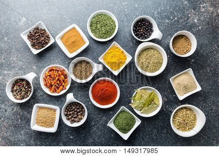 Various dried herbs and spices in ceramic bowls. Top view.