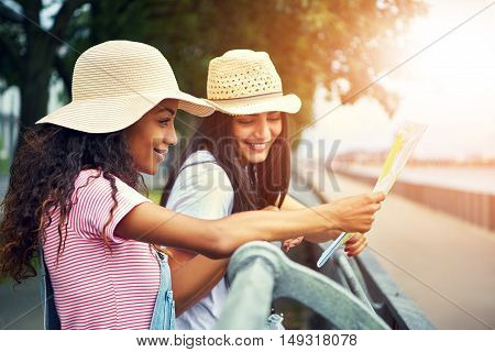 Women outside leaning against jogging path railing wear straw hats and smile while they read a map