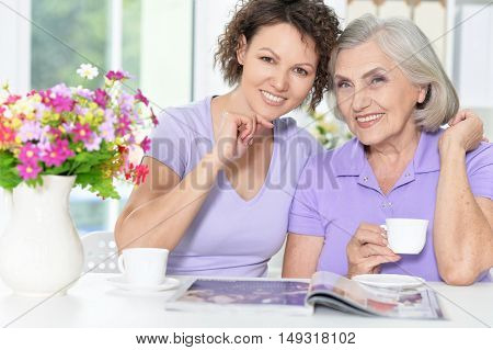 Portrait of Senior woman with daughter with magazine at home