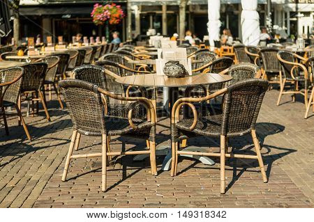 Beautiful outdoor restaurant with small round tables and wicker chairs in in Alkmaar, Holland
