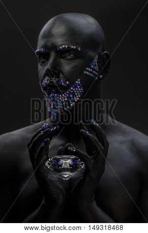 Man painted in black color with rhinestones hair beard and eyebrows