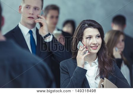 Two people standing in the crowd and talking on the phone