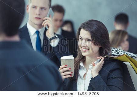 Smiling woman standing in the crowd and drinking coffee