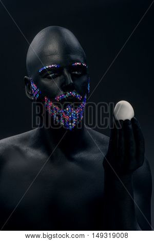 Man painted in black color with rhinestones hair beard and eyebrows holding egg
