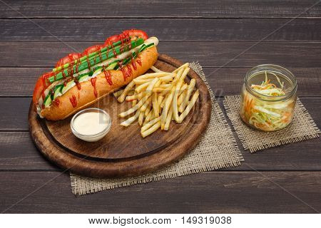 Hot dog and french fries. American fast food restaurant cuisine - hotdog with mustard, mayonnaise and ketchup, paper pack with potato chips and salad at wooden desk on table.