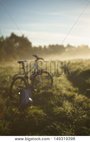 Bicycle and backpack on grassy track by foggy morning blurred image