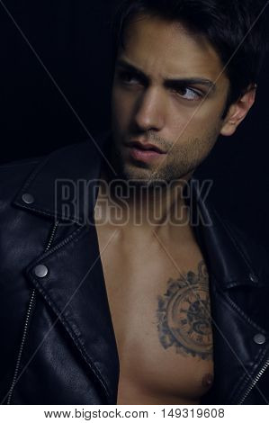 Handsome bad boy wearing a leather jacket over a black background