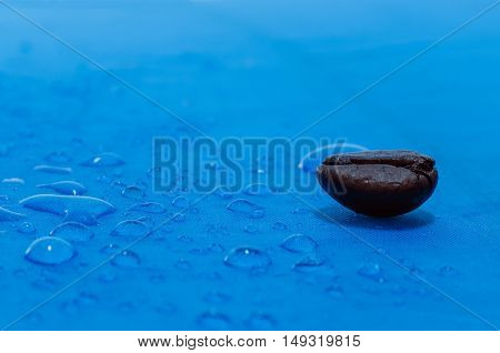Water droplets on blue fiber waterproof fabric with coffee beans