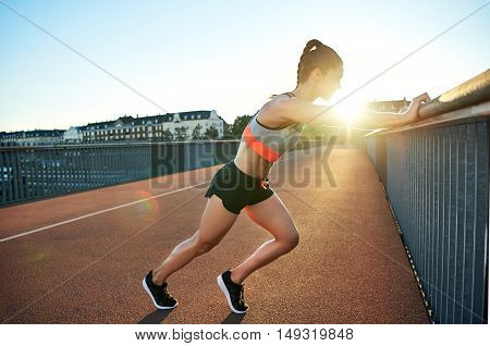 Female jogger stretches against bridge railing as sun pokes over her shoulders
