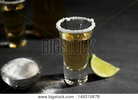 Gold tequila shot with lime and salt on gray background