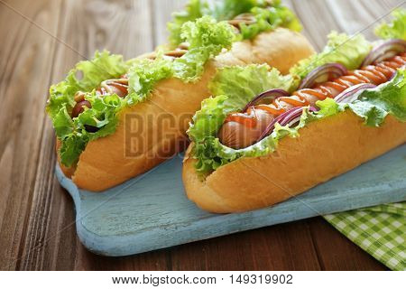 Delicious hot dogs on wooden board