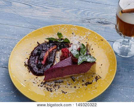 Restaurant dessert meal closeup. Delicious raspberry cheesecake served with berry sauce, grated chocolate and mint leaf. Sweet dish on blue rustic wood table.