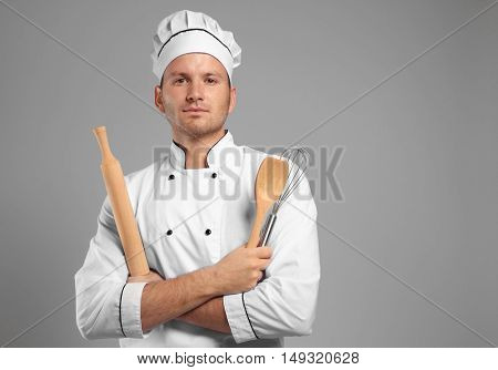 Young chef cook with cutlery on grey background