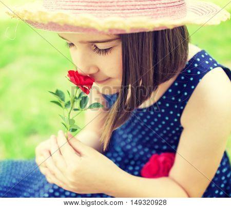 Portrait of little beautiful girl is smelling flowers